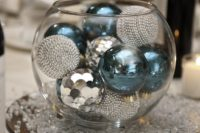 04 a glass bowl filled with turquoise and silver ornaments is a budget-friendly centerpiece