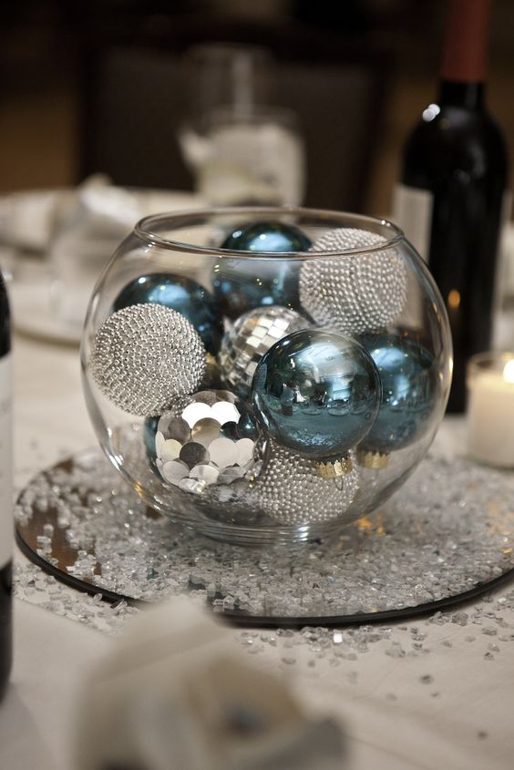 a glass bowl filled with turquoise and silver ornaments is a budget-friendly centerpiece