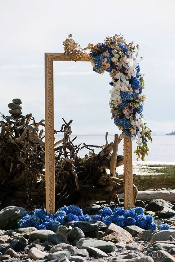 a gorgeous coastal backdrop with a vintage gilded frame and veyr lush blooms in blush and blue looks breathtaking
