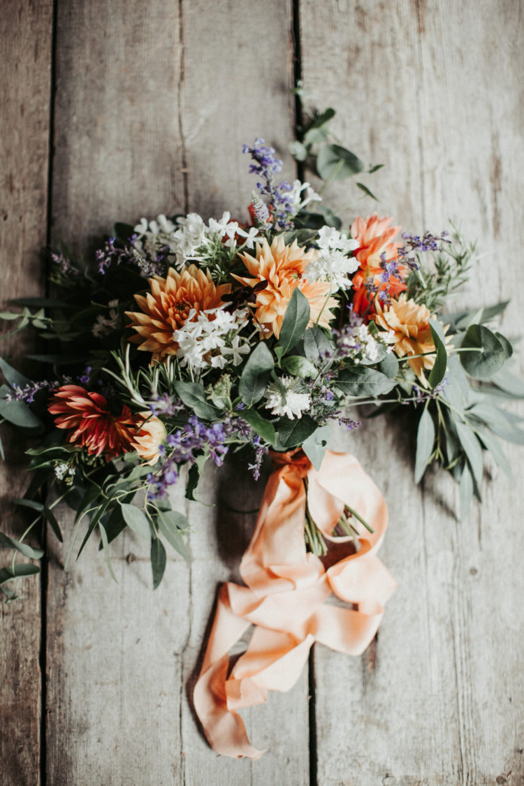 The bridal bouquet was done in lavender, orange and white blooms and greenery