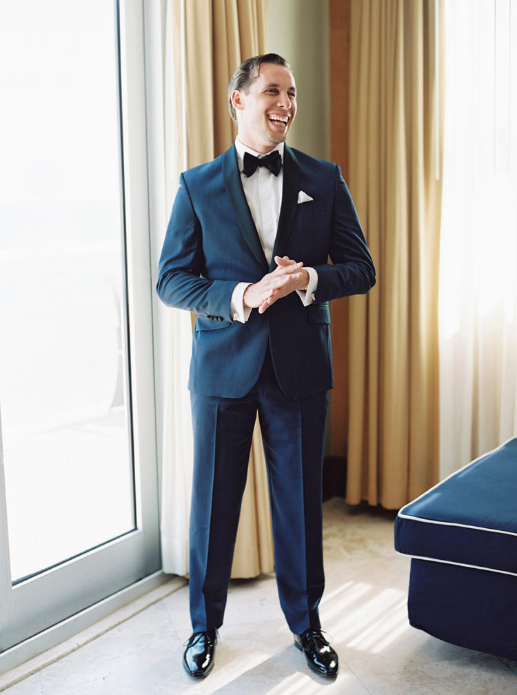 The groom was wearing a navy tuxedo with black lapels and black shoes