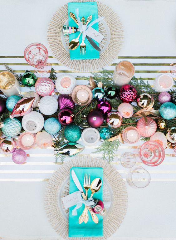 a colorful and glitter ornament table runner on fir branches and ornaments for each place setting
