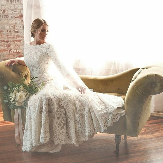 a lace applique wedding gown with a bateau neckline and logn sleeves is a timeless option that never goes out of style
