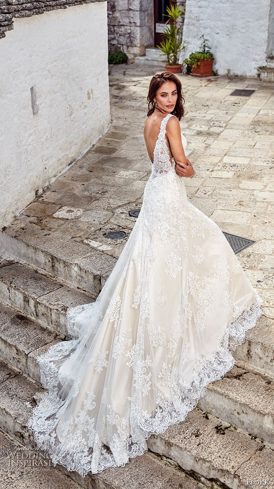 a romantic sleeveless lace wedding dress with an open back and a train