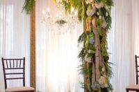 05 a vintage picture frame with a crystal chandelier, birch branches, pinecones, greenery and blooms for a woodland feel indoors