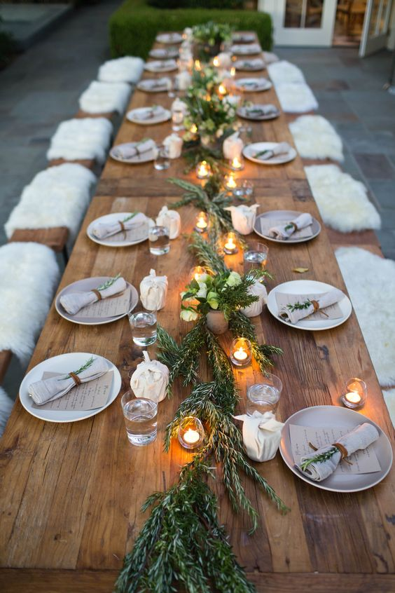 a winter tablescape with a fresh greenery runner, candles and faux fur benches