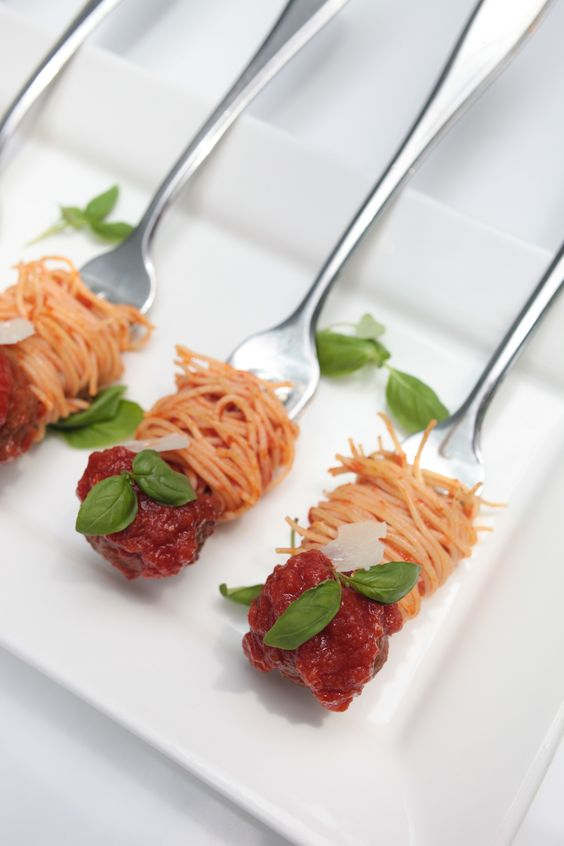 spaghetti and meatballs on forks with greenery is a cool way to serve some meat