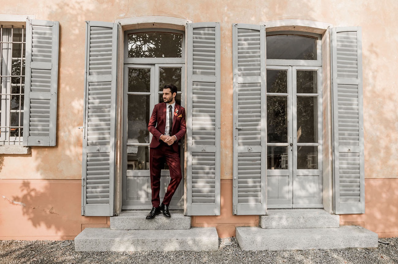 The groom was wearing a burgundy wedding suit and black shoes