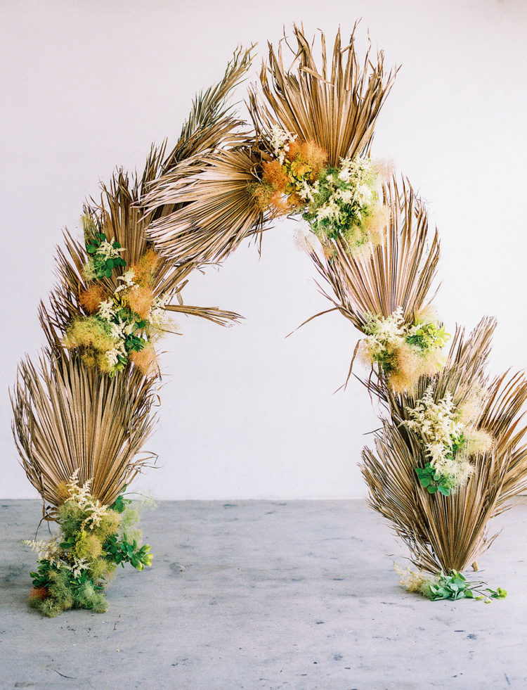 The wedding arch was done with dried palm leaves and moss, which brings in a fall feel