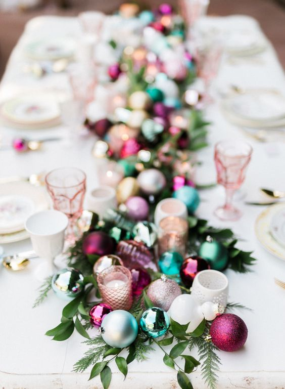 a gorgeous table runner made of candle holders, greenery and colorful Christmas ornaments