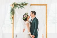 06 an ethereal draped fabric backdrop, an oversized picture frame decorated with greenery and blooms