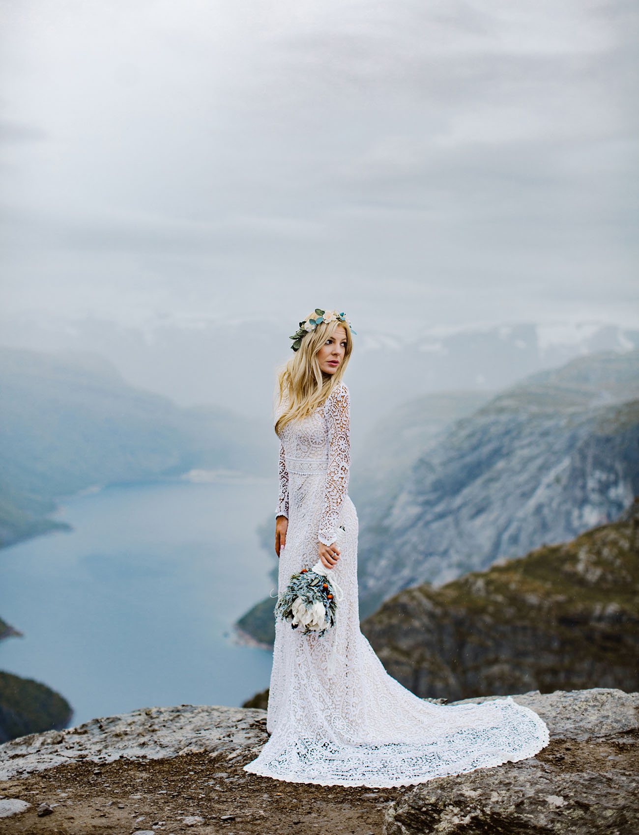 She was wearing a boho lace wedding dress with a high neckline, long sleeves and a train, her waist was highlighted with a sash