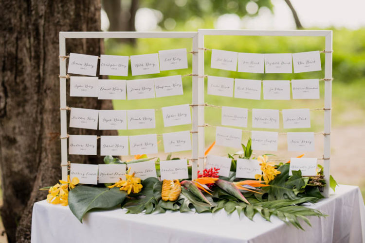The seating chart was lushly decorated with tropical leaves and bold blooms