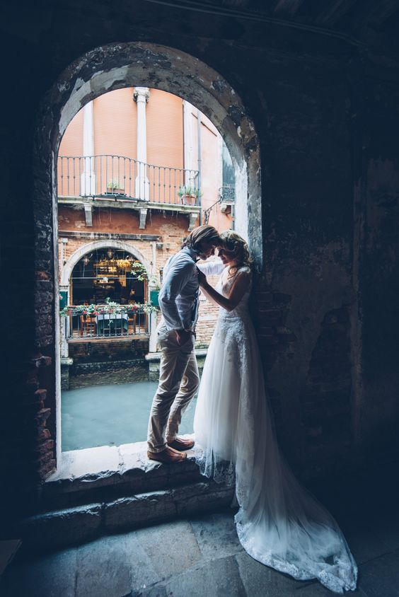 a couple in an arch in Venice looks really beautiful and the shot is very romantic
