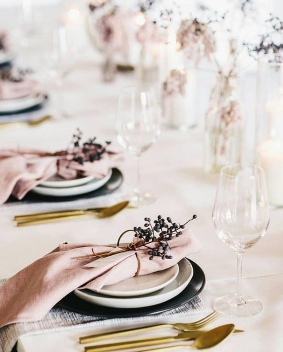 a cute tablescape with pink napkins, blooms, berries and black chargers