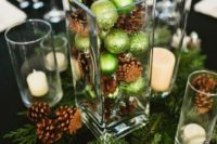 07 a glass vase with pinecones and green ornaments placed on fir branches and with candles look very festive