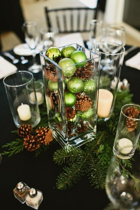 a glass vase with pinecones and green ornaments placed on fir branches and with candles look very festive