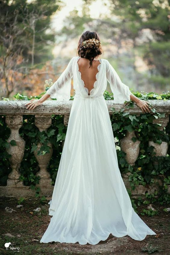 an ethereal wedding dress with a cutout back with lace, half sleeves with lace and a train