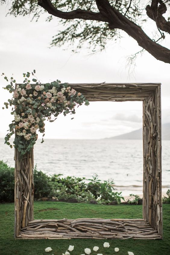an oversized driftwood frame with blush roses and greenery for a coastal wedding