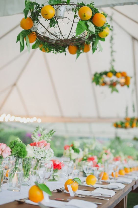 fun chandeliers with oranges and lush foliage to spruce up your wedidng decor