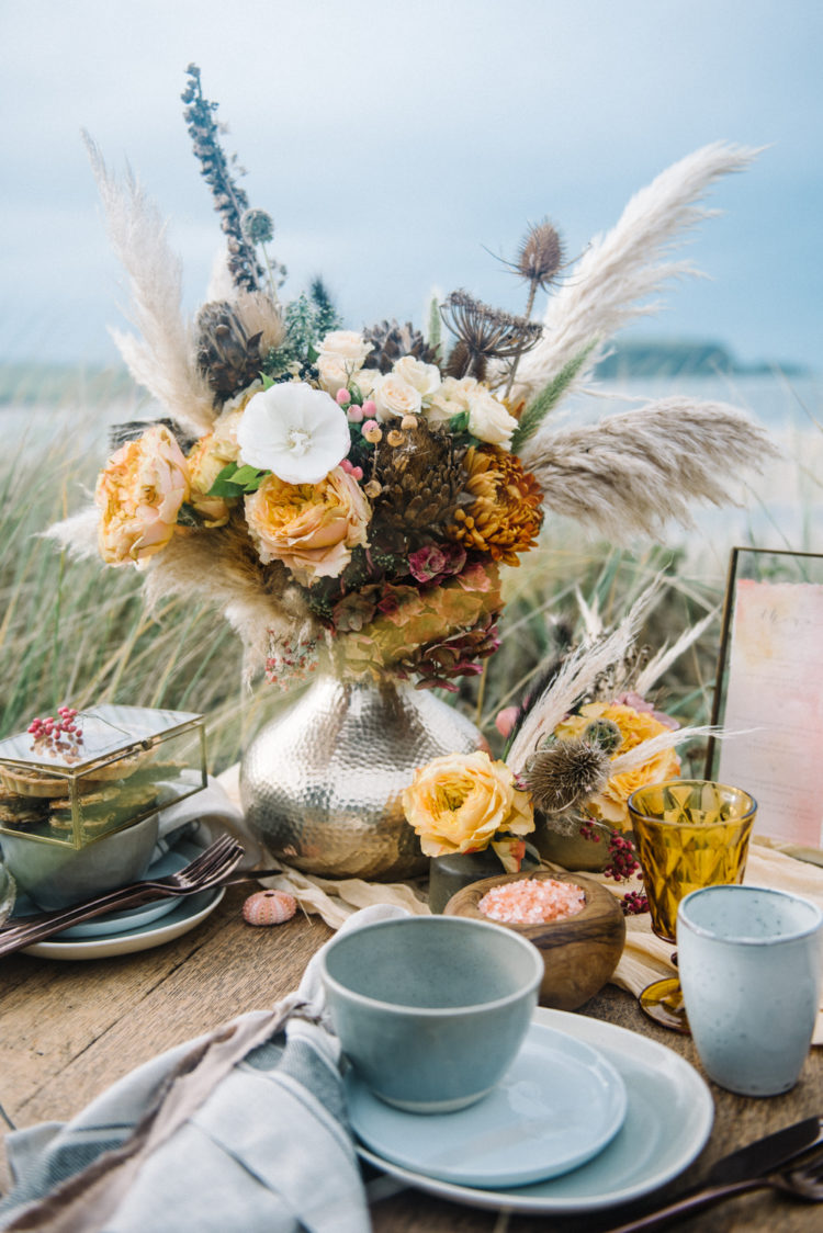 The florals were done in fall and earthy colors, the crockery was grey, and you can see shells and sea salt on the table