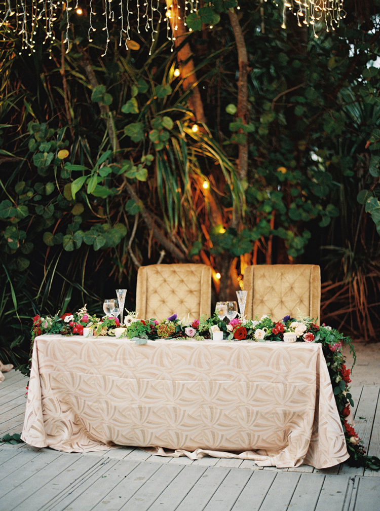 The sweteheart table was decorated with a colorful floral garland and a textural tablecloth