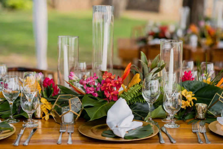 The tables were decorated with runners of tropical leaves and colorful flowers, geometric candle holders