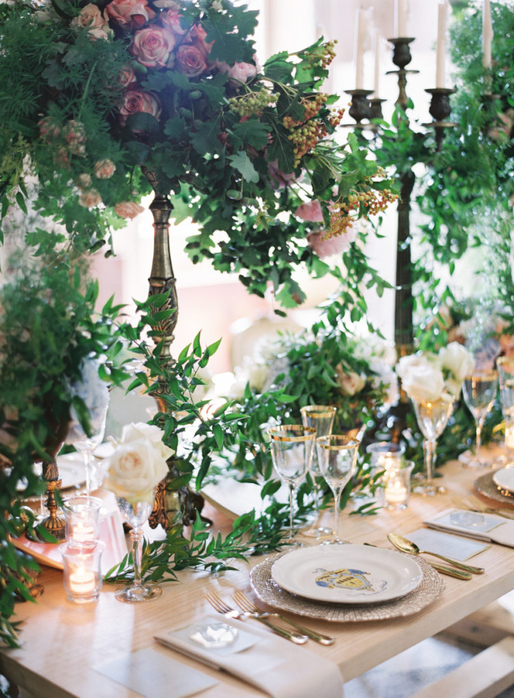 The wedding tablescape was done with lush greenery and blooms, with candles and gold rim glasses
