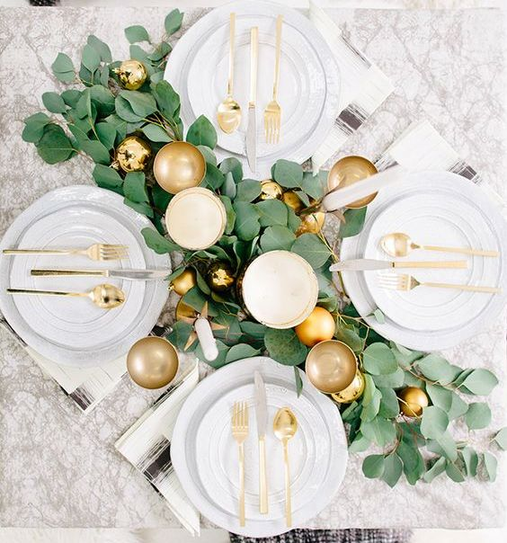 a glam tablescape with a foliage table runner, gold ornaments and glasses