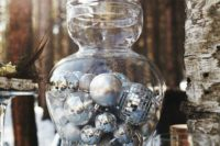 08 a large glass jar filled with various silver ornaments is a great idea for a centerpiece