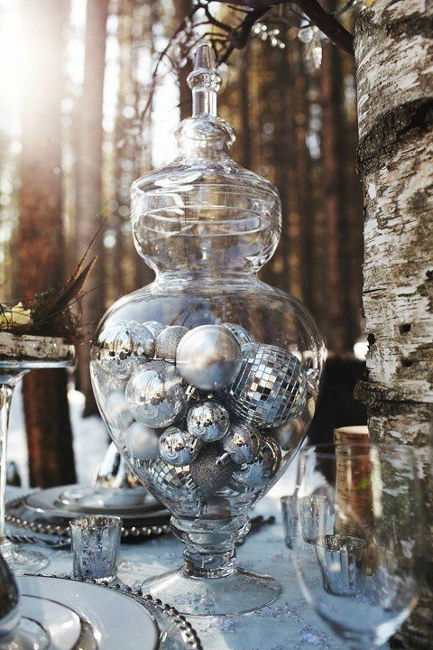 a large glass jar filled with various silver ornaments is a great idea for a centerpiece