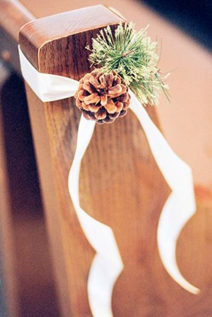 a pinecone with evergreens and white ribbon to decorate the aisle