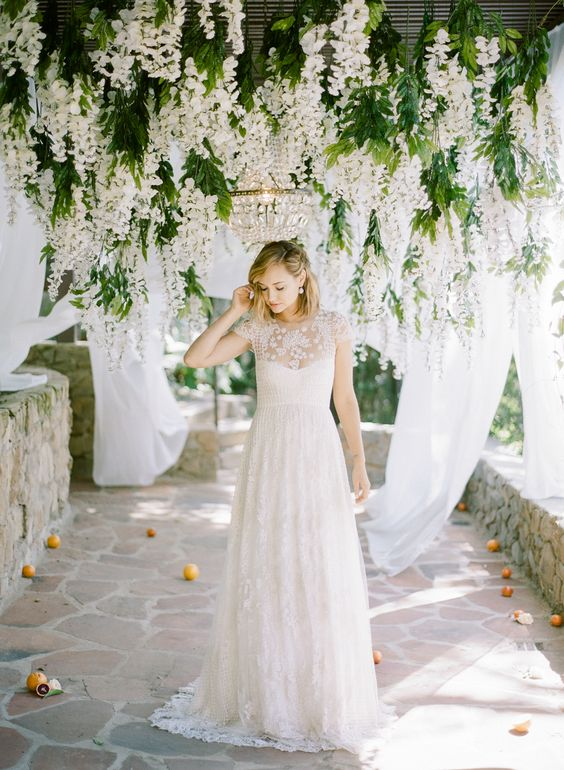 an ethereal short sleeve wedding dress with a sweetheart neckline, lace appliques and a lace skirt