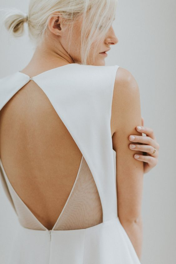 an open geometric back with sheer details is ideal for a modern or minimalist bride