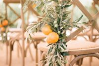 08 decorate chairs in the ceremony space with olive branches and oranges for a gorgeous look