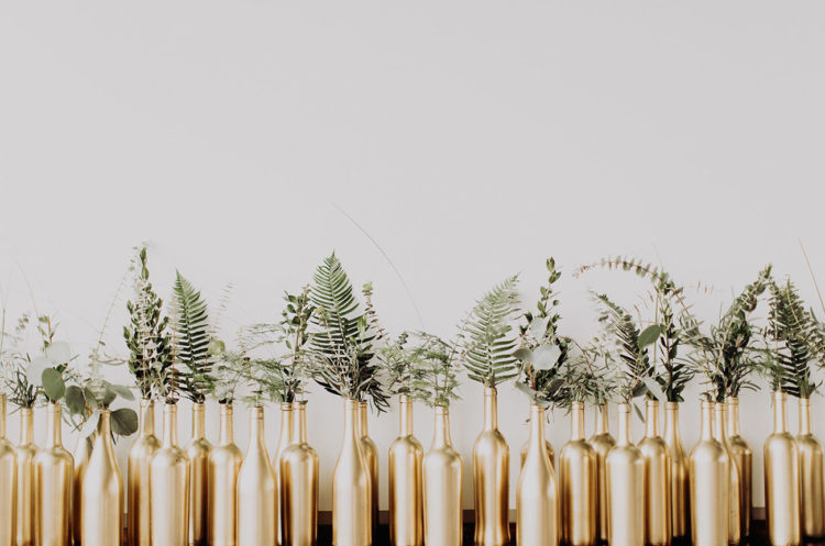 The centerpieces were made of gold bottles and fresh greenery