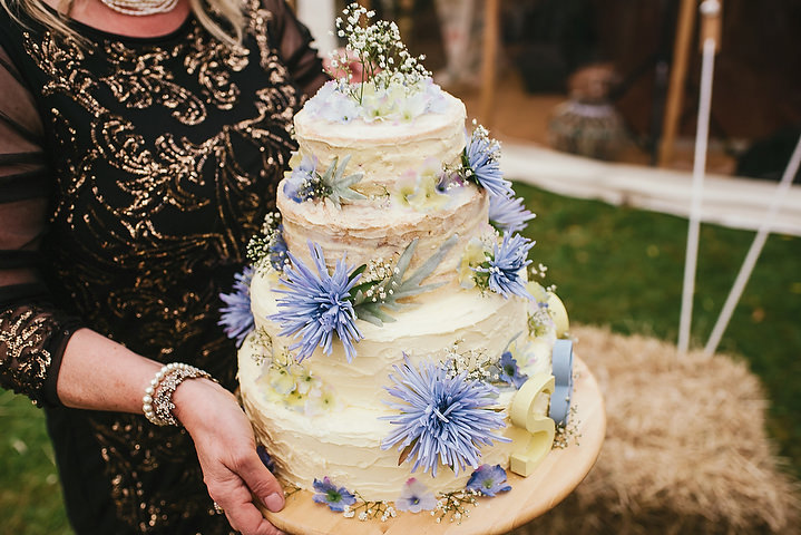 The wedding cake was made by the groom's mother, it was topped with blue flowers and letters