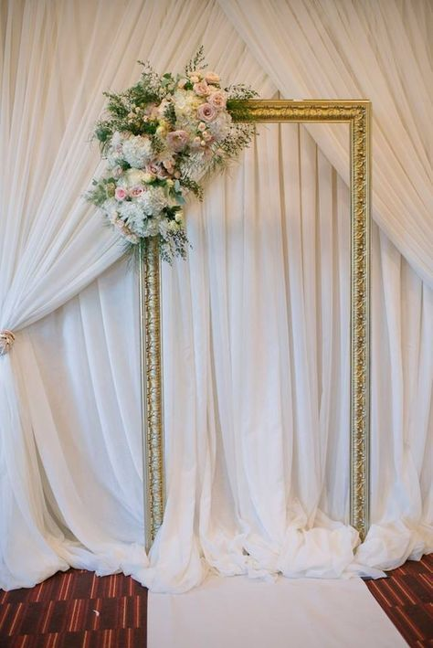 draped curtains, a gilded picture frame decorated with lush blooms for a refined wedding backdrop