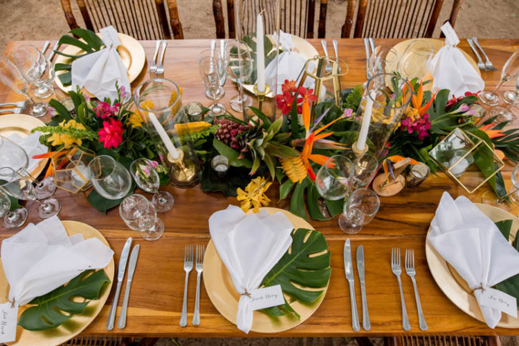 Gilded chargers and tropical leaves added chic to the table