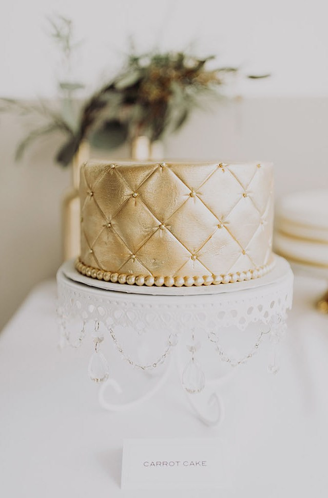 The wedding cake was a gold one, served on a refined stand with hanging crystals
