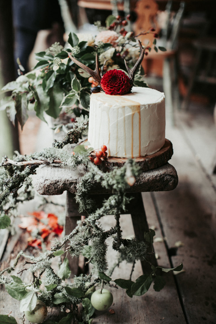 The wedding cake was frosted white, with drip, a dahlia and antlers and felt boho and fall-like