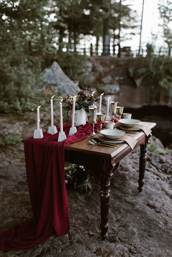 The wedidng table was done with a red fabric runner, pink candles in concrete candle holders and silver goblets
