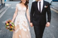 10 a blush wedding dress with an illusion neckline, sleeves and white lace appliques all over the dress