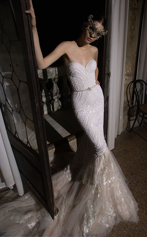 a breathtaking embellished strapless mermaid wedding dress with a layered tail and a mask