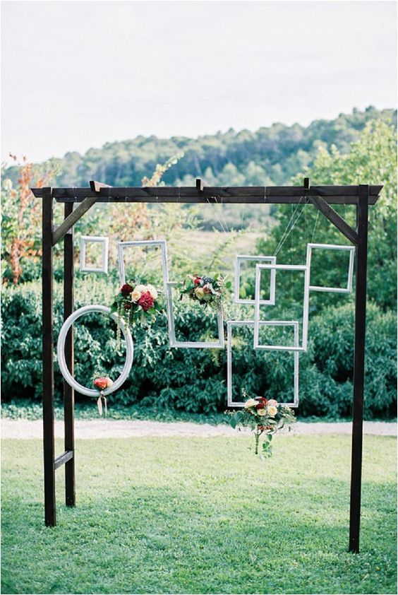 a chic arch with hanging picture frames with fresh blooms is great for a backdrop