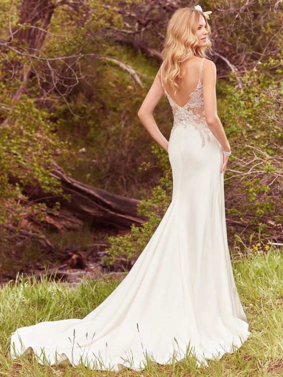 lace applique embellished wedding dress with a partly cutout back and a train