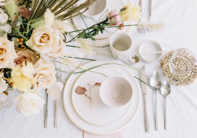 The tablescape features unique pottery and blush and neutral blooms