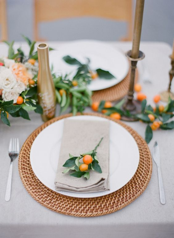 a chic table runner with foliage and kumquats, and fresh kumquats for markign every place setting