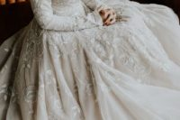 11 a modest A-line wedding dress with long sleeves, lace appliques, a bateau neckline