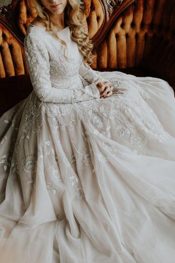 a modest A-line wedding dress with long sleeves, lace appliques, a bateau neckline